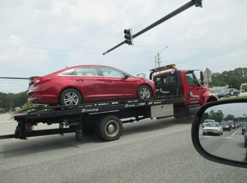 Flatbed Tow truck with a car on it in jacksonville florida