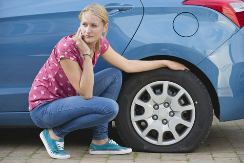 Lady with a flat tire on the phone next to her car
